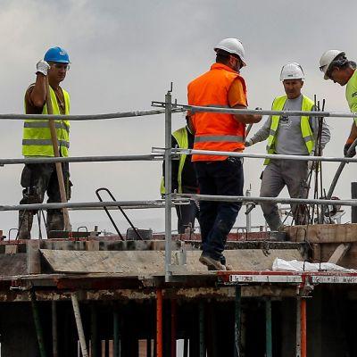 Kuusi rakennusmiestä talon katolla keltaisissa ja oransseissa liiveissä, kypärät päässä.