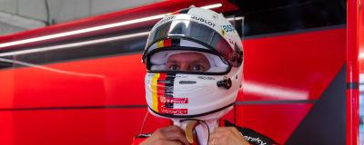 Sebastian Vettel pysslar med sin hjälm.