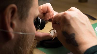 Närbild av urmakare Kari-Matti Ratsula som reparerar ett ur