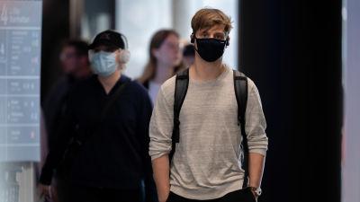 Mies kävelee kohti kameraa kasvoillaan musta suun ja nenän peittävä hengityssuojain. Miehen takana kävelee nainen lippalakki päässä jolla on myös hengityssuojain. Taaempana kävelee kohti muita ihmisiä, joilla ei ole hengityssuojamia.