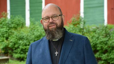 Karl af Hällström framför ett rött lider och gröna buskar. Han småler.