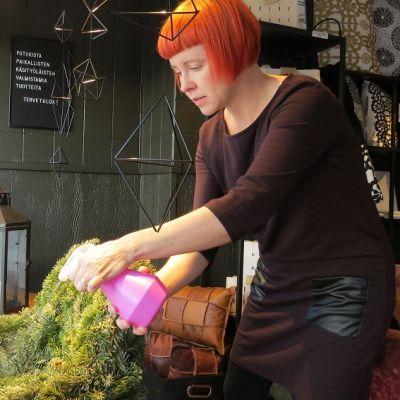 Punatukkainen nainen liikkeen näyteikkunassa sumutepullon kanssa.