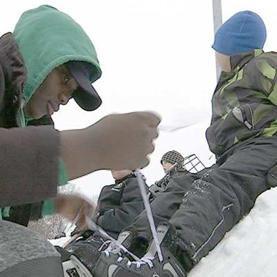 Oulun Kastellin koulun maahanmuuttajien valmistavan luokan oppilaat auttavat alaluokkalaisia luistimien nauhojen sitomisessa.