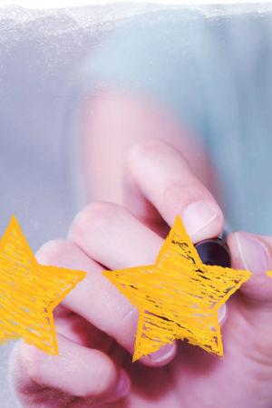 Kuvassa viisi arviointitähteä ja naisen käsi.
