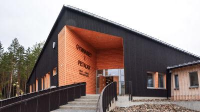 Trappa som leder upp till svart skolbyggnad i trä.
