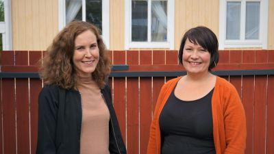 Två kvinnor står framför ett brunt staket.