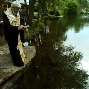 Pappi pyhittää vettä Pyhän Henrikin pyhiinvaelluksen kolmantena päivänä.