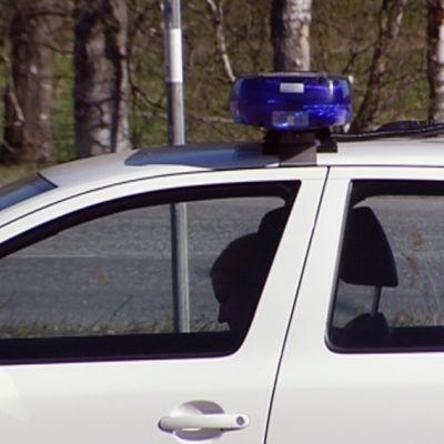 Mies istuu poliisiauton takapenkillä.