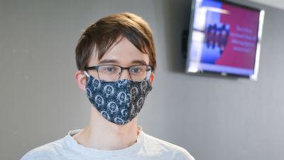 Johan Malmberg i blått munskydd framför en tv-skräm och en grå vägg.