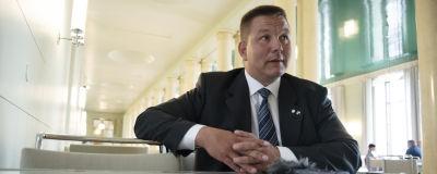 Riksdagsledamoten Juha Mäenpää (Sannf) intervjuas i riksdagen. Han har händerna i kors och han sitter vid ett bord och har en mikrofon framför sig.