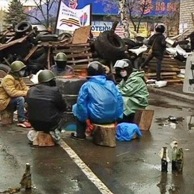 Ihmisiä barrikadin vierellä tulipöntön ympärillä.