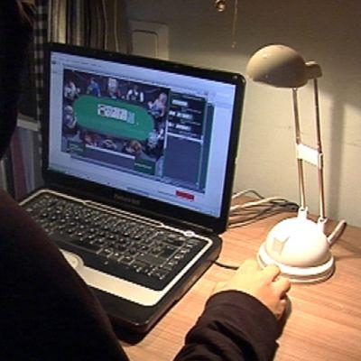 Tummiin pukeutunut henkilö pelaa nettipokeria tietokoneella.