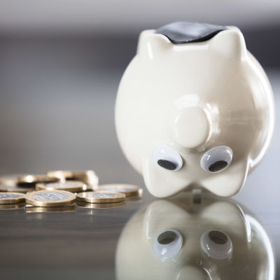 En vit spargris med stora ögon är vänd upp och ner på en blank yta och bredvid den ligger några en eurosslantar.