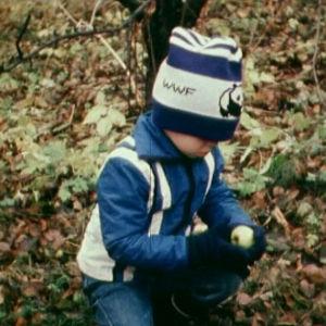 Poika syksyisten lehtien keskellä omena kädessään