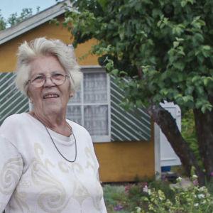 Äldre dam i vit tröja och svartvitrutiga byxor står vid porten till sin koloniträdgård. I bakgrunden gulmålad stuga och ett stort äppelträd.