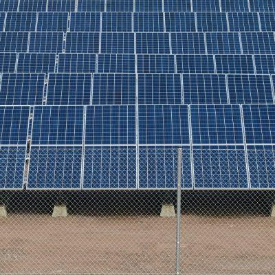 Aurinkopaneeleja aidan takana rivissä Haminan Mäkelänkankaalla.