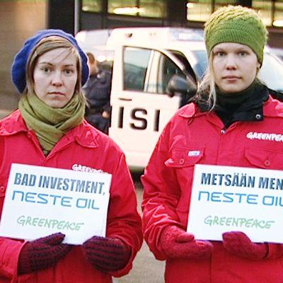 Kaksi Greenpeacen mielenosoittajaa Neste Oilin pääkonttorin ulkopuolella.