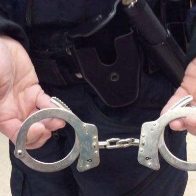 Poliisi esittelee käsirautoja.