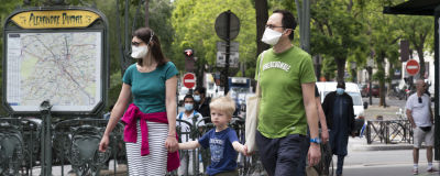 äiti, isä' ja lapsi kävelevät metroaseman edessä
