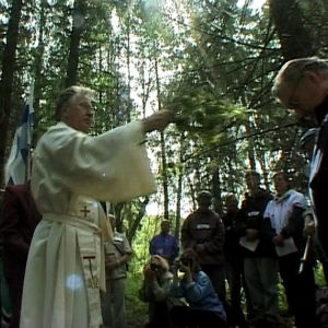 Katolinen isä pirskottaa vettä pyhiinvaeltajan päälle vaelluksen neljäntenä päivänä.