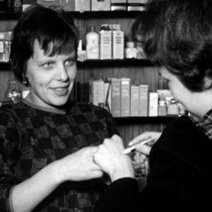 Nainen kokeilee kosmetiikkaa kaupassa
