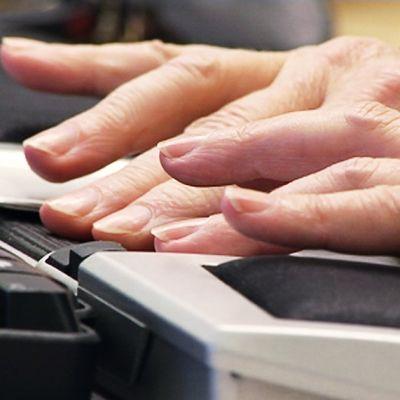 Henkilö kirjoittaa tietokoneella, lähikuva käsistä näppäimistöllä.
