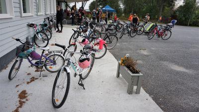 Cyklar framför en vit byggnad.