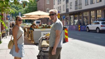 En kvinna och en man står på trottoaren på Kristinegatan. Mellan sig har de en barnvagn.