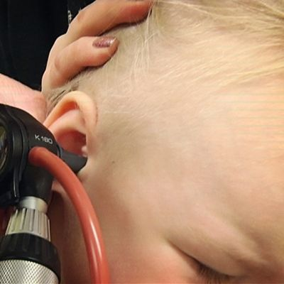 Lääkäri tarkastaa lapsen korvaa