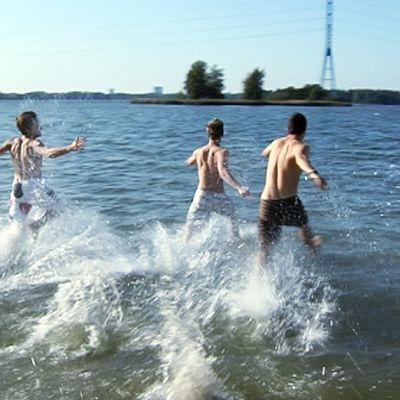 Neljä miestä juoksee veteen uimarannalla.