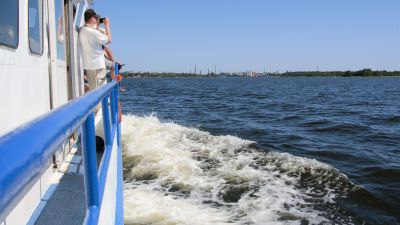 En man tittar i en kikare från en båt. I bakgrunden ses Vasa.
