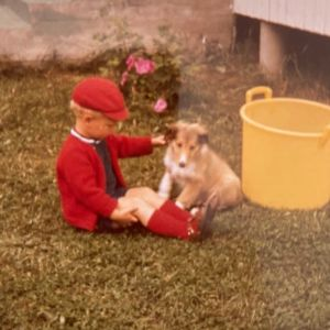 Punaista paitaa, nilkkasukkia ja hattua käyttävä poika istuu koiran kanssa nurmikolla. Taustalla iso vesiämpäri.