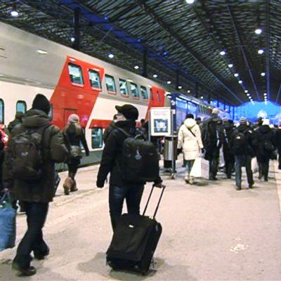 Matkustajia nousemassa juniin Helsingin rautatieasemalla.