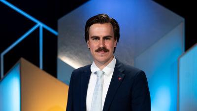 Matias Mäkynen, En ung man med kortare hår och mustasch tittar in i kameran.