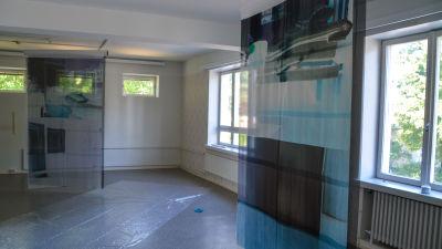 Tygbitar med print av fotografier som hänger ner från taket i ett annars tomt rum.