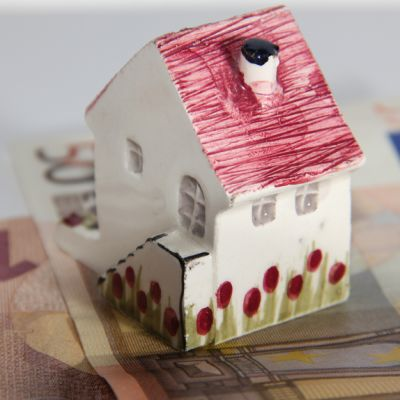 Kuvassa pieni talo seteleiden päällä.