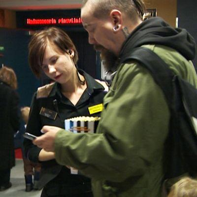Työntekijä tarkastaa lippuja elokuvateatterin ovella.