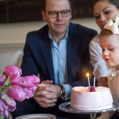 2-vuotias prinsessa Estelle ja hänen vanhempansa syntymäpäiväkakun äärellä.
