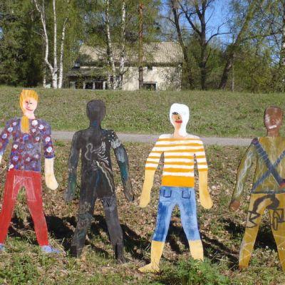 Vanerille maalattuja ihmishahmoja Louhitalon pihapiirissä.