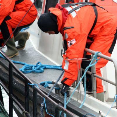 Meripelastaja kiinnittää venettä köydellä.