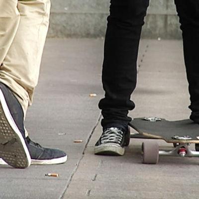 Två par fötter på en gård. En av personerna har en skateboard.