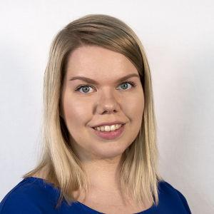 Sinisiin pukeutunut toimittaja Anna Nevalainen hymyilee kameralle.
