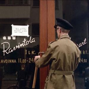 Kippari (Smerts Siren) yrittää turhaan ravintola Kolmeen kruunuun Liisankadulla Helsingissä elokuvassa Lauantaileikit (1963)