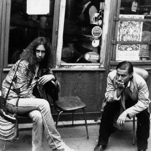 Kaksi nuorta miestä istuu 70-lukuisen kyläkuppilan ulkopöydässä.