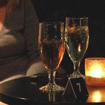 En tjej sitter bredvid två glas öl.