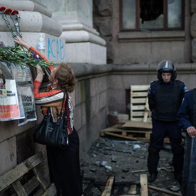 En kvinna för en blomsterhälsning till offer i brand i Odessa