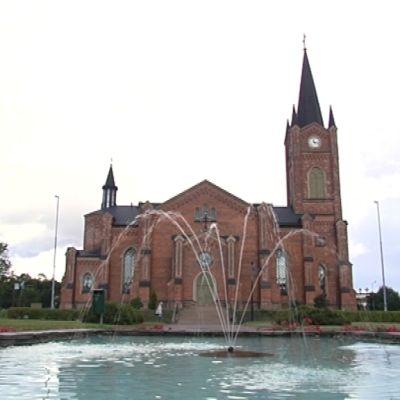 Lovisa kyrka i solsken, vattenfontän i förgrunden