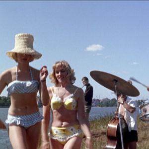 Jazzyhtye ja bikineihin pukeutuneet daamit jammailevat saaressa elokuvassa Lauantaileikit (1963)