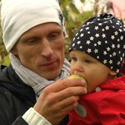 Olli Ilander äter äppel tilsammans med sin son