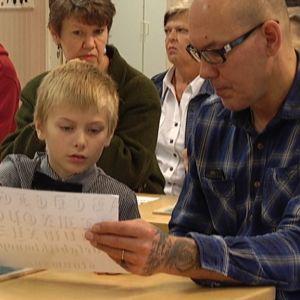 Pappa och son funderar på gammaldags skrivstil